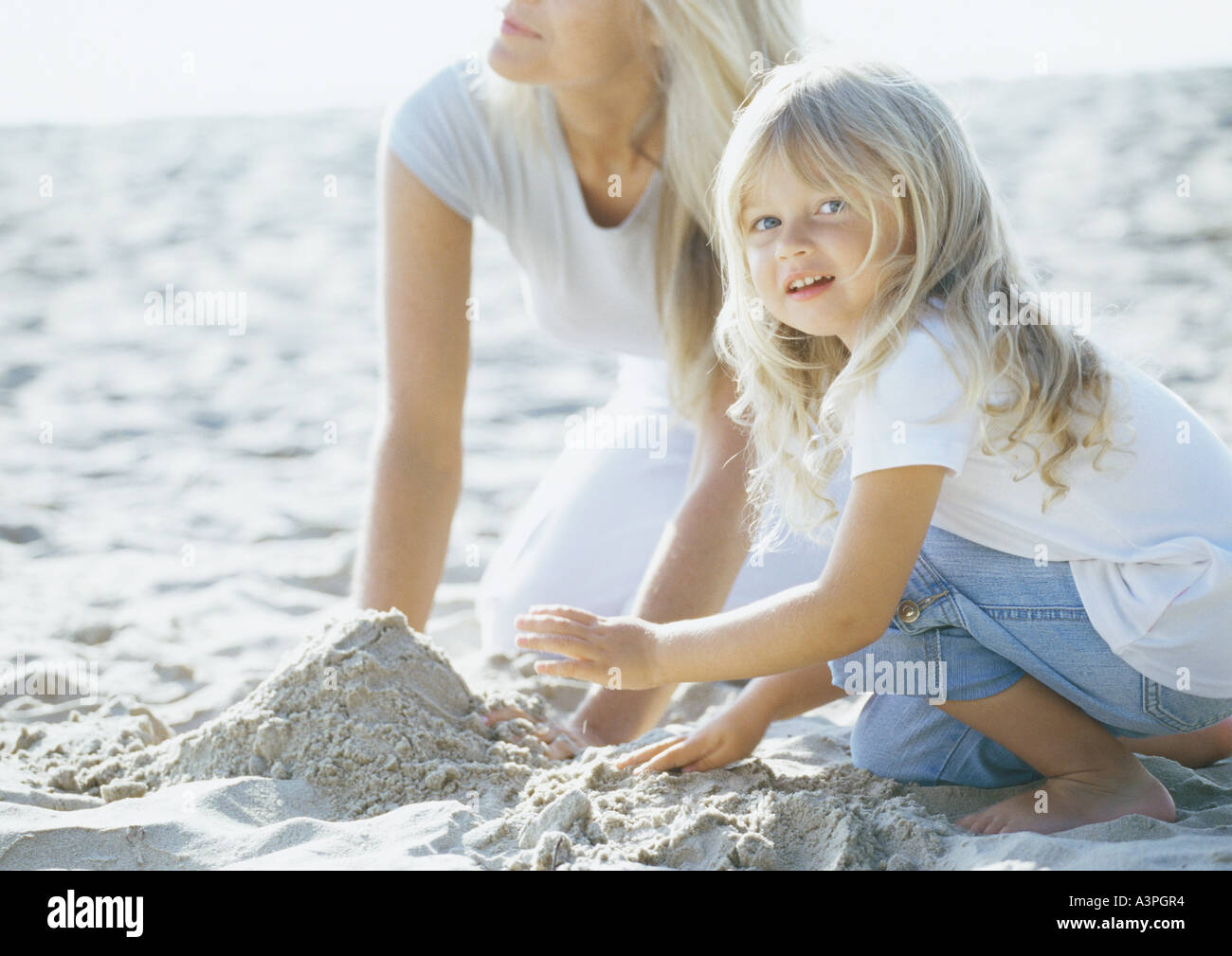 Girl and mother playing in sand - Stock Image