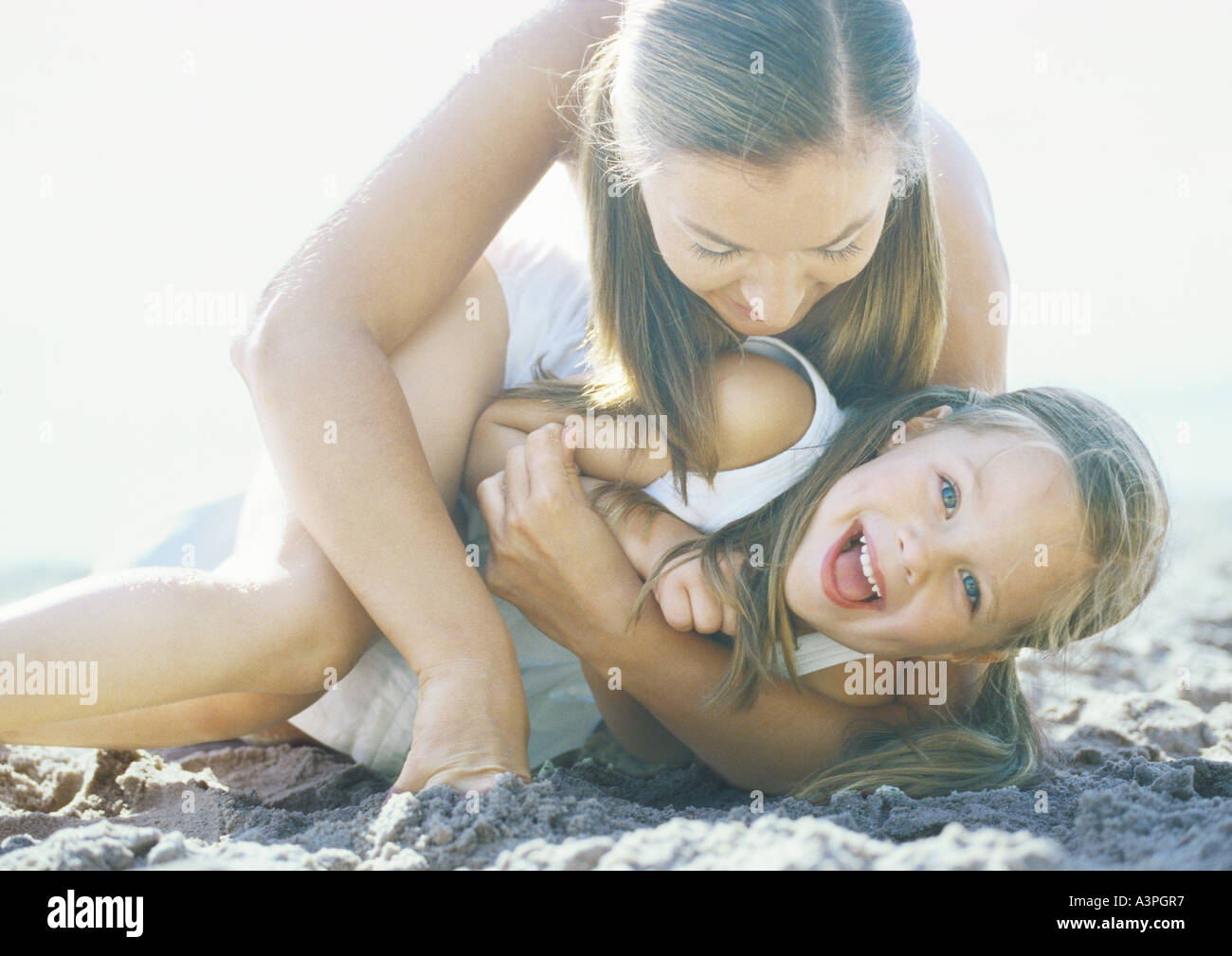Woman holding daughter on sand, laughing - Stock Image