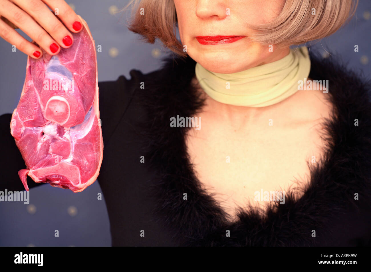 Woman holding a slice of raw meat with a look of disgust on her face - Stock Image