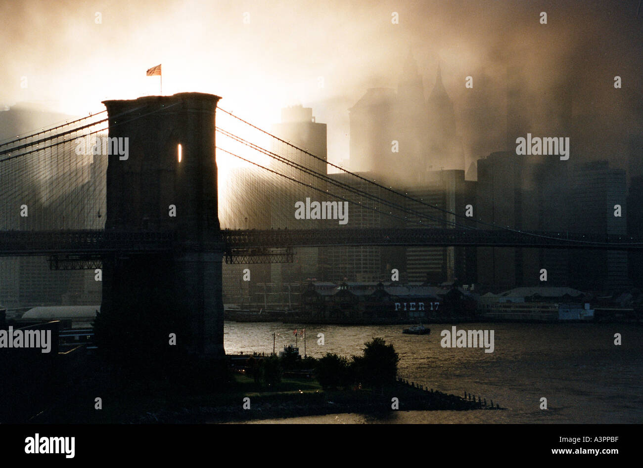 Sunset through the smoke of the WTC terrorist bombings of September 11 2001 frames the pylons of the Brooklyn Bridge - Stock Image