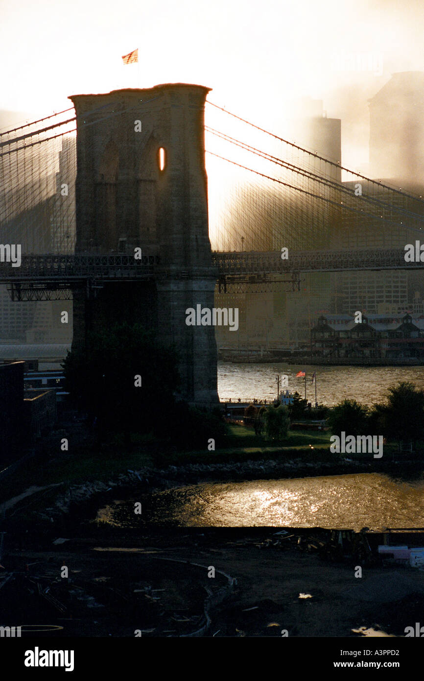 Sunset rays through smoke frame the East pylon of the Brooklyn Bridge after the terrorist attacks of September 11 2001 - Stock Image
