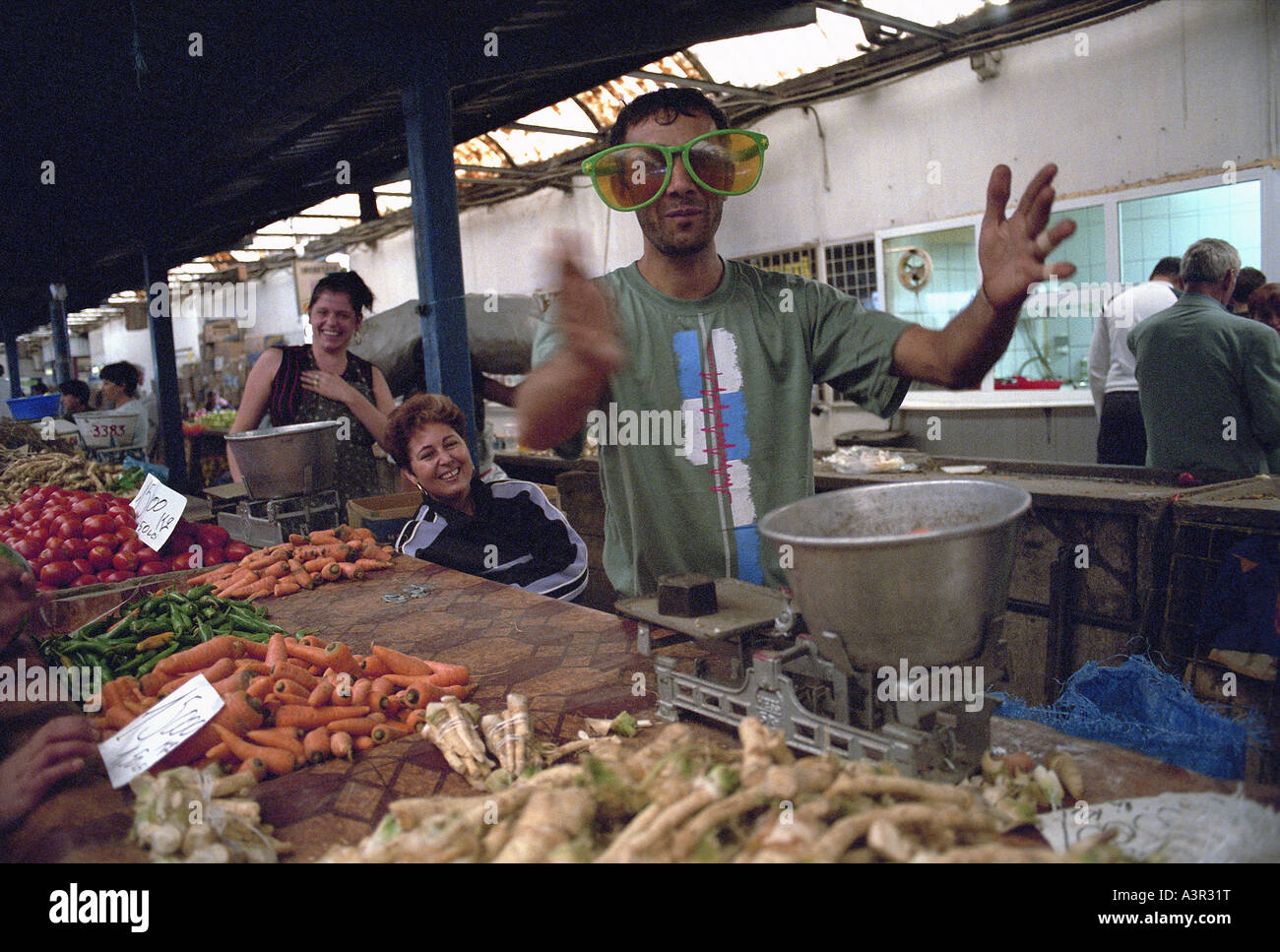 Vegetable seller in funny oversize glasses at a market, Bucharest, Romania - Stock Image