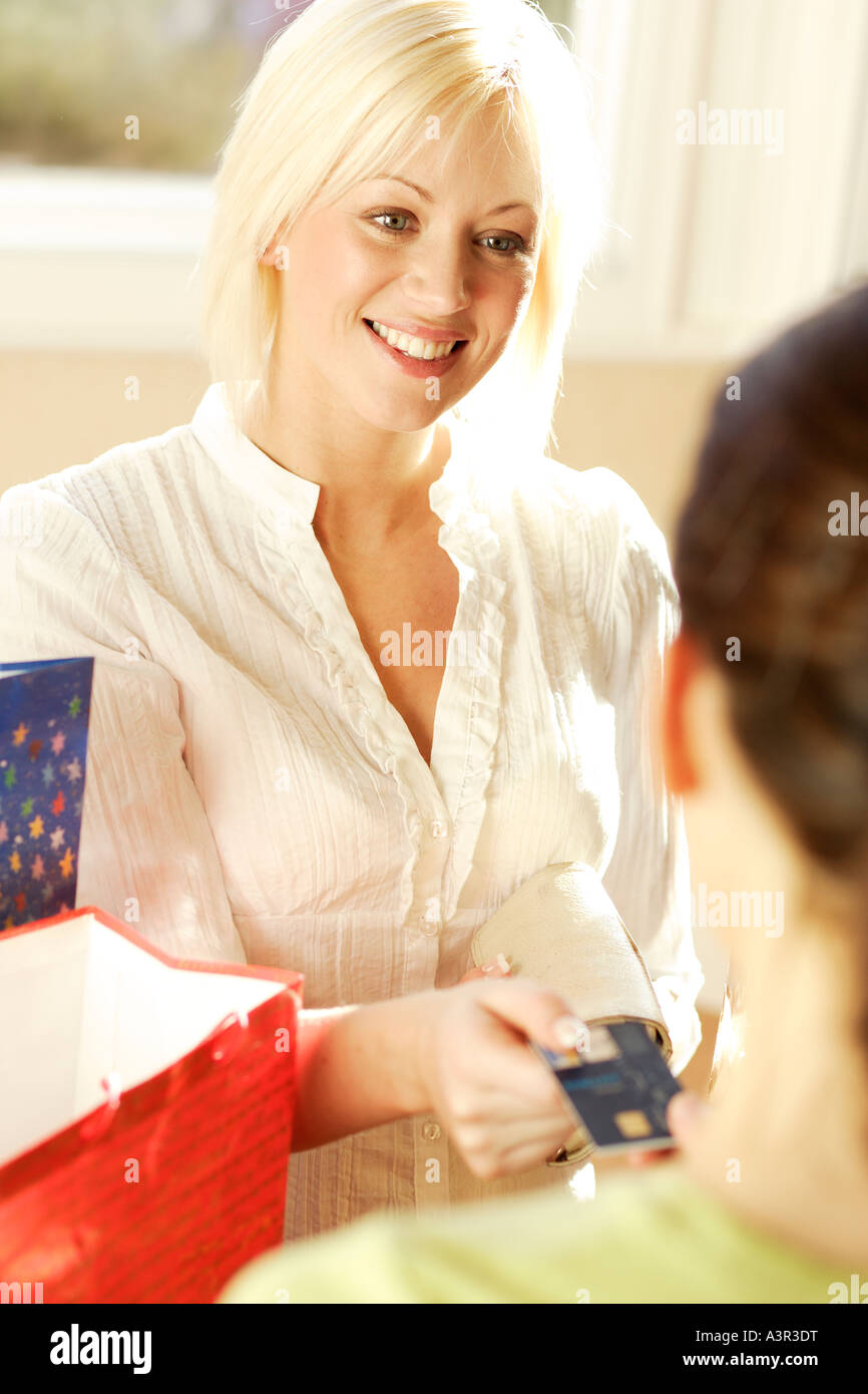 Young blonde woman paying for goods in shop - Stock Image