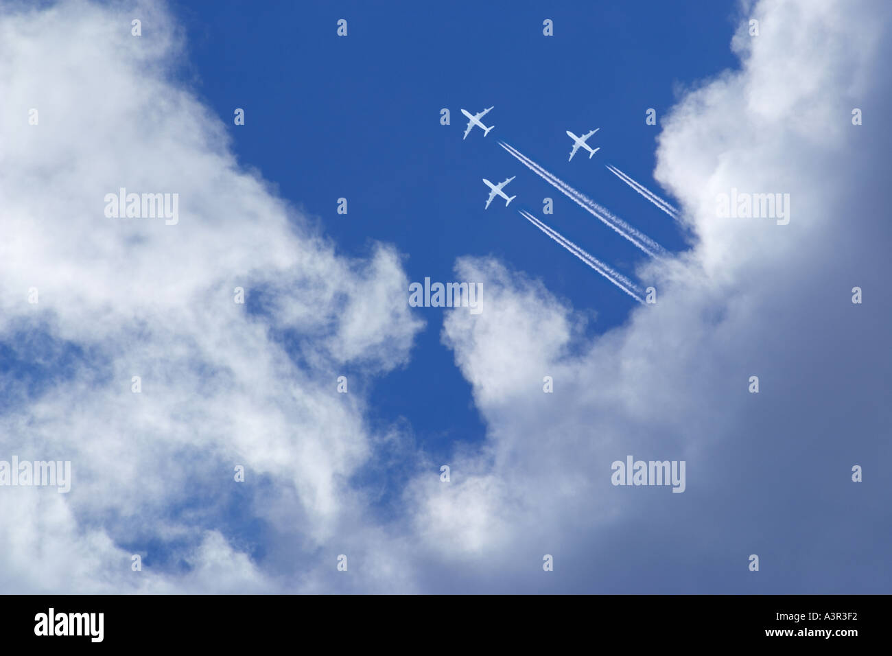 three white passenger airplanes with vapor trails in blue sky