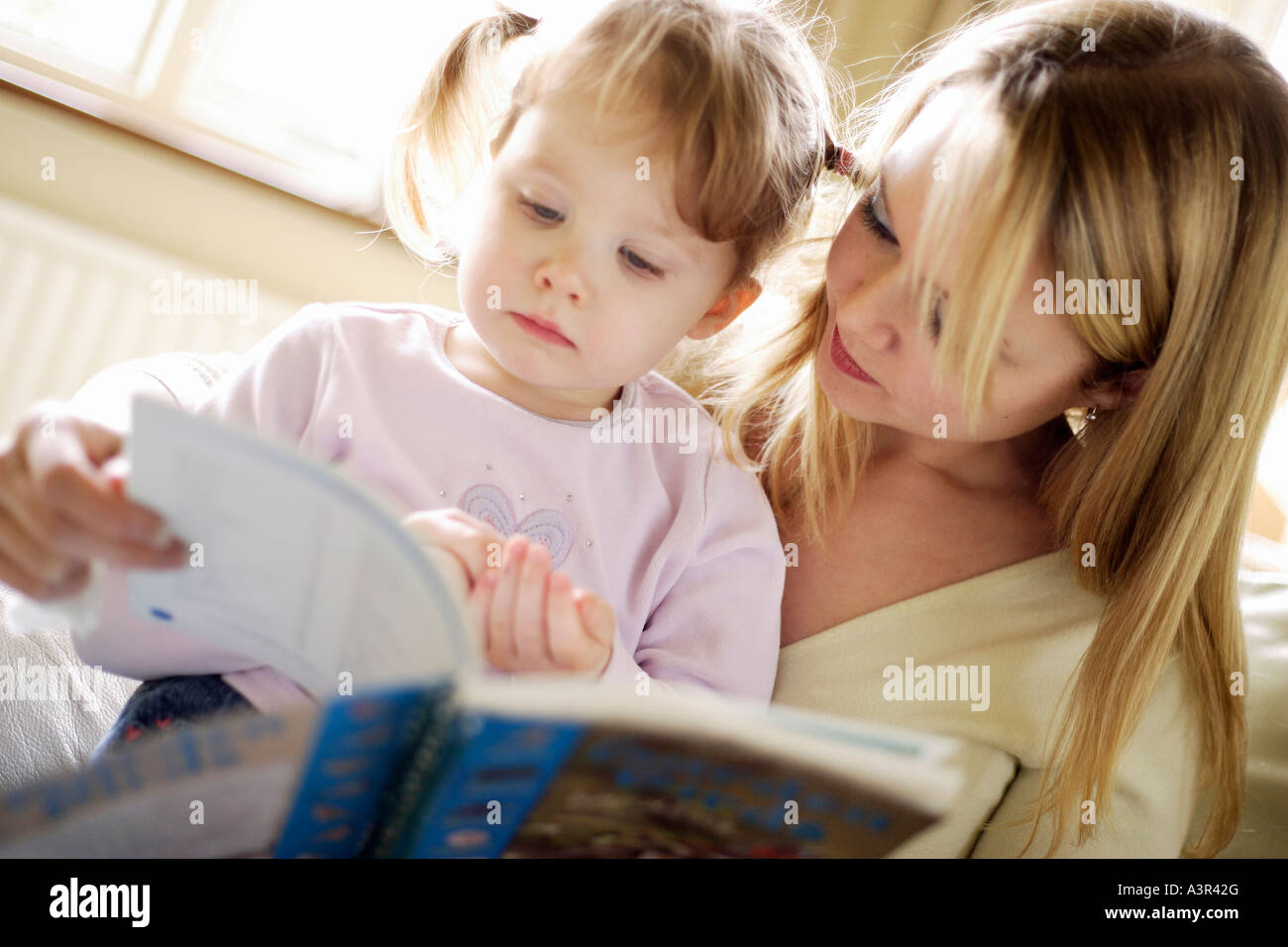 Mother reading with daughter - Stock Image