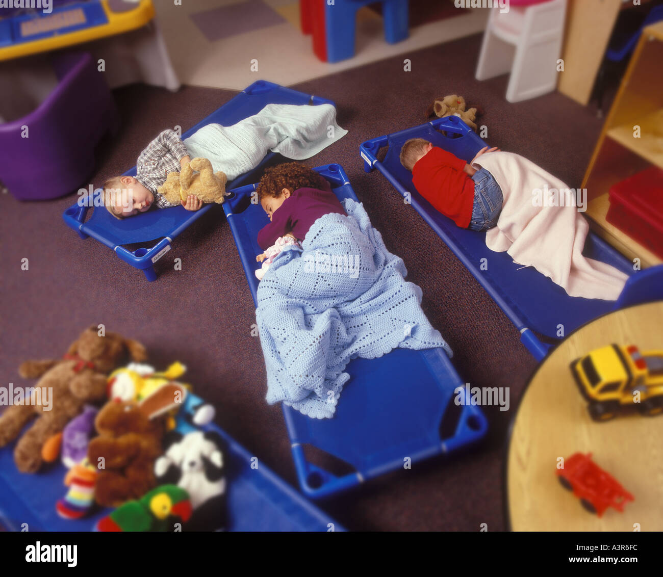 Children Sleeping On Floor Mats At A Daycare Center Stock Photo