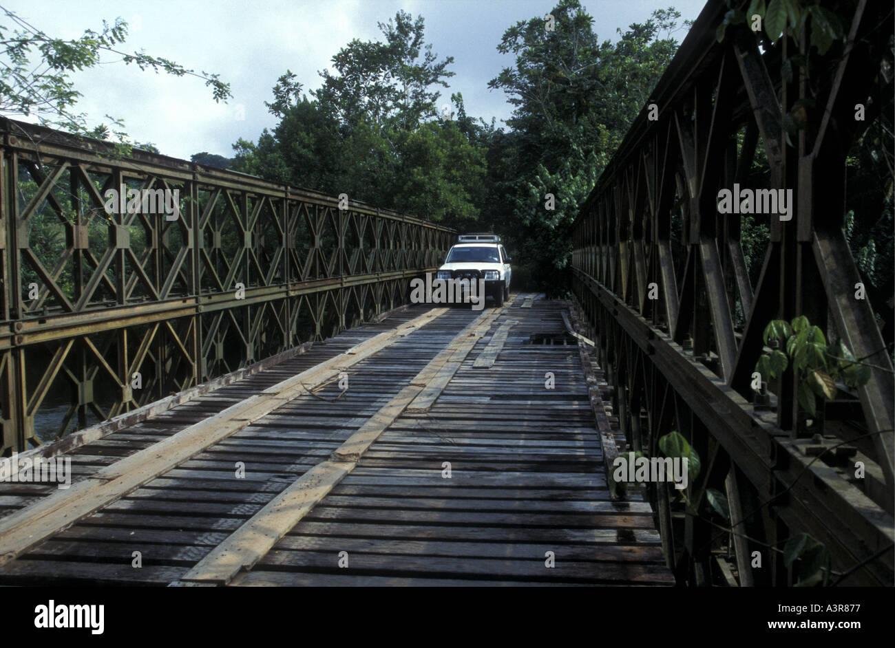 White four wheel drive vehicle crossing dilapidated Bailey type bridge Ivindo National Park Gabon West Africa - Stock Image