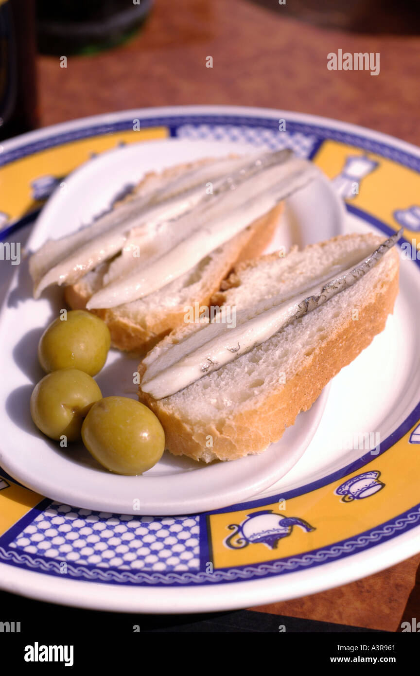 Tapas of marinated anchovies and olives Boquerones al Vinagre - Stock Image