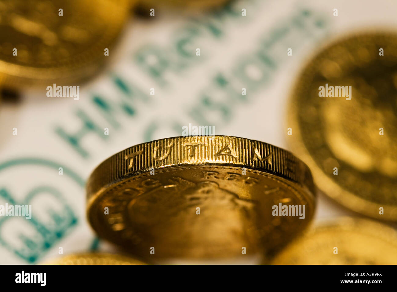 HM Revenue Customs document surrounded by pound coins - Stock Image
