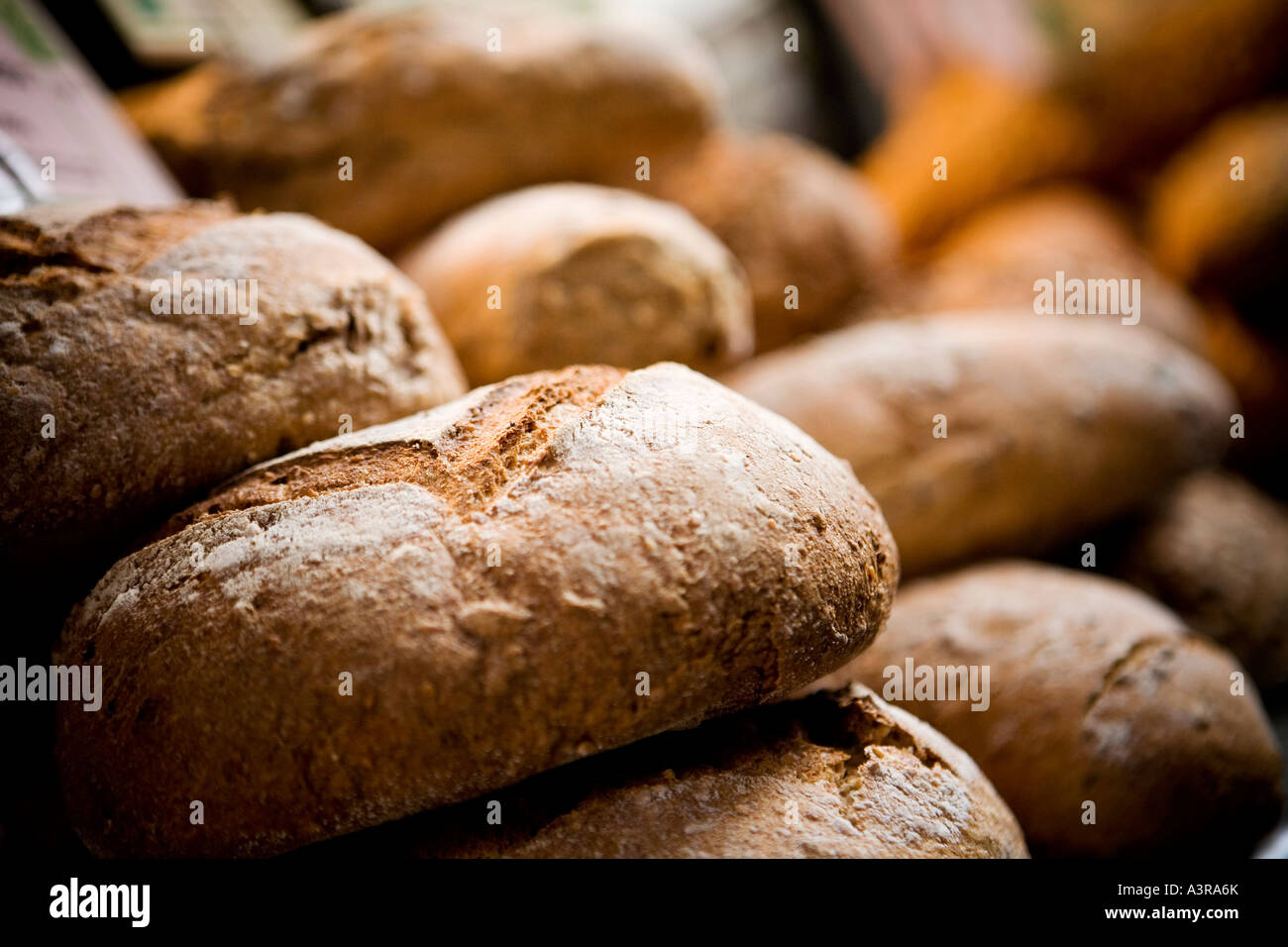 Freshly baked loaves of bread on a bread stall in London Borough market - Stock Image