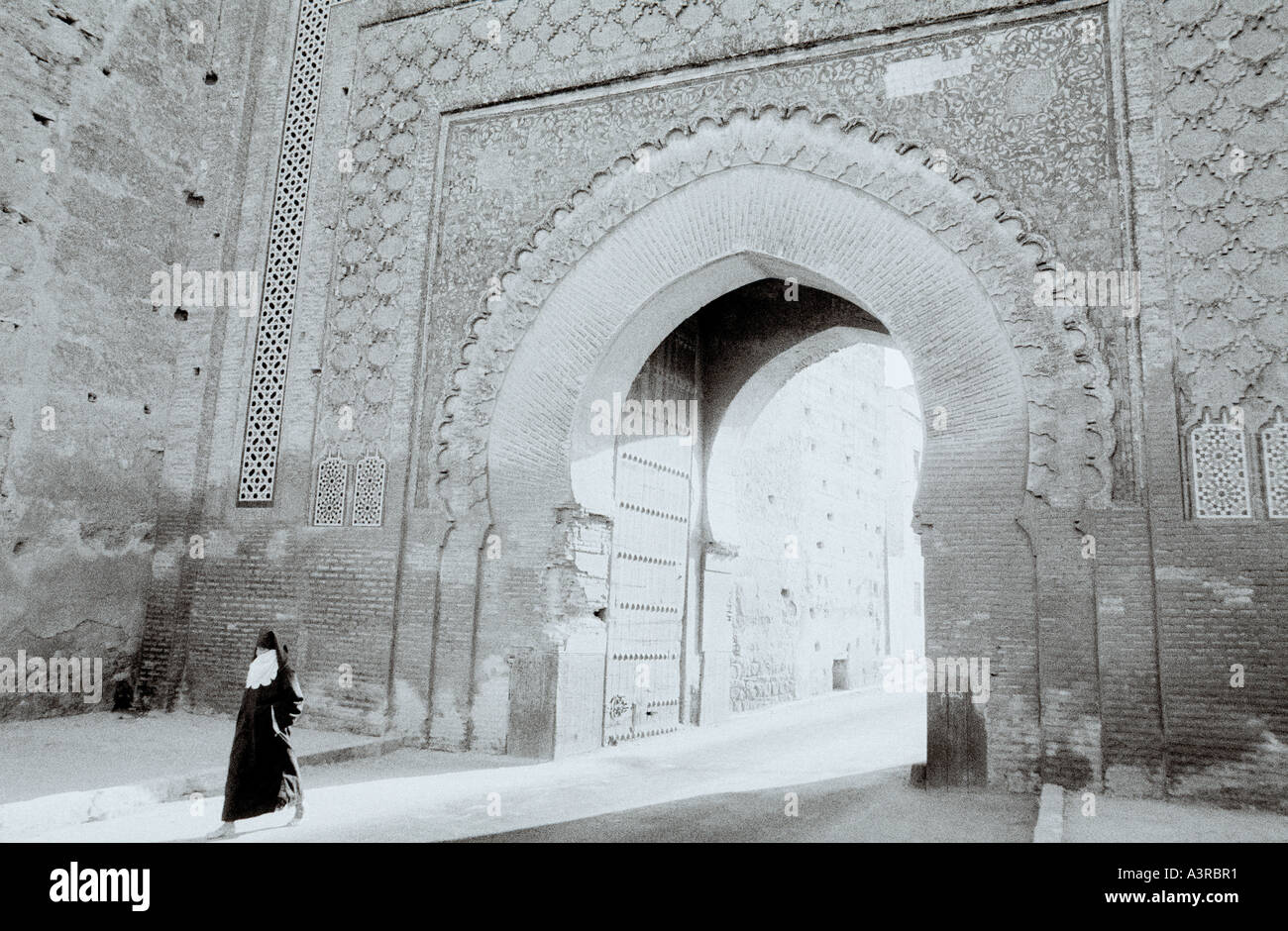 A woman in yashmak face veil walks through the Bab Mansour Gate in the Meknes Casbah Medina in Morocco in the Maghreb in North Africa Sahara. Travel - Stock Image