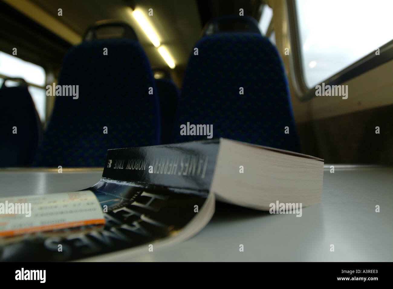 A book resting on the table of a train carriage - Stock Image