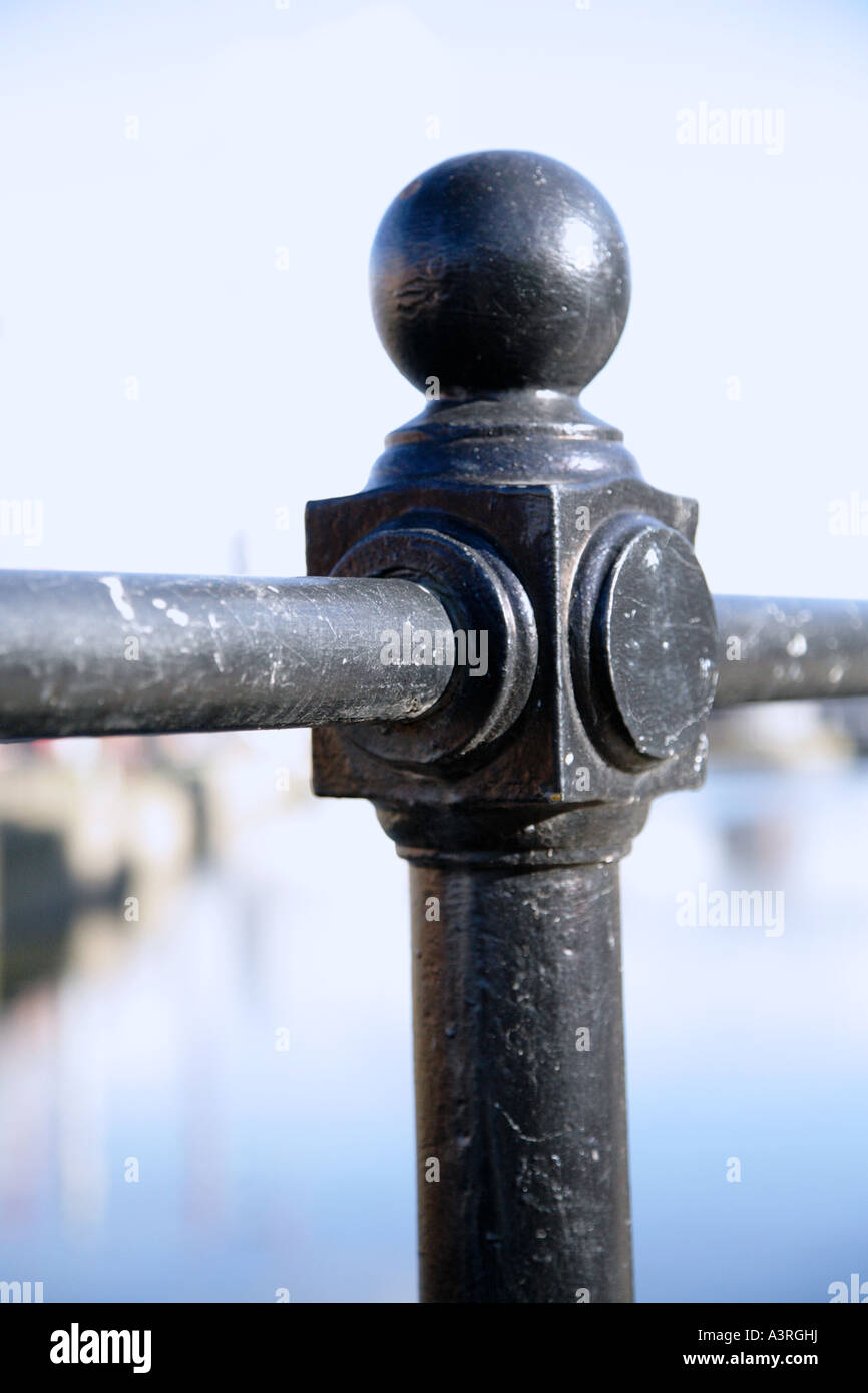 Close up of a scuffed railing post against a blue sky - Stock Image