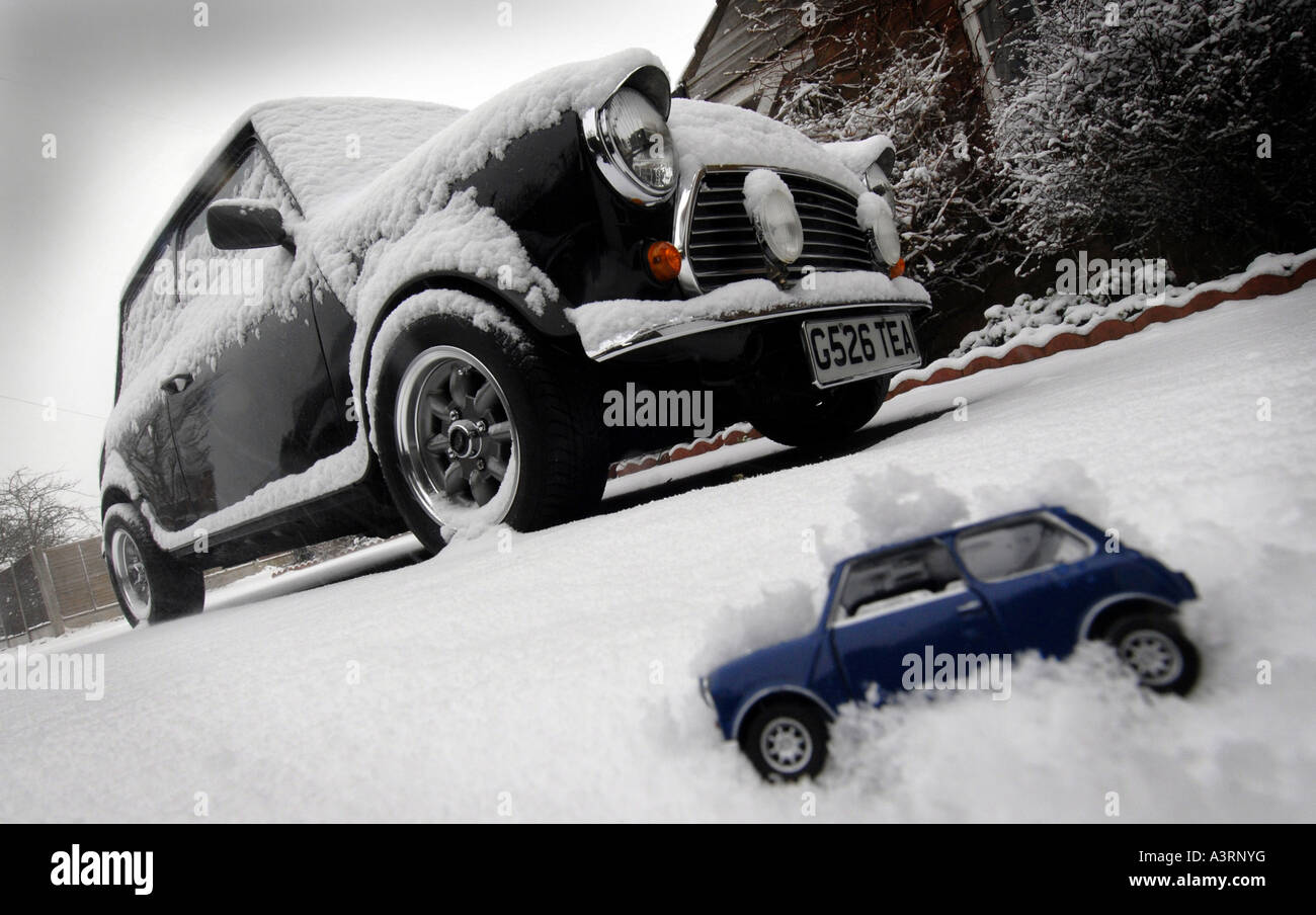 CLASSIC MINI CAR IN SNOW WITH MODEL MINI CAR RE WINTER MOTORING DRIVING COSTS SERVICING MAINTENANCE UK - Stock Image