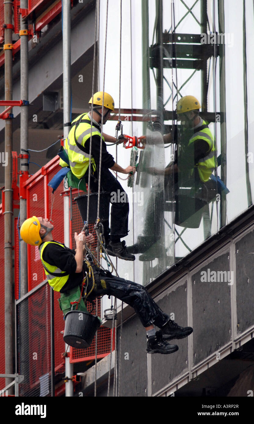 ABSEILING WINDOW CLEANERS WORK ON A BIRMINGHAM CITY BUILDING RE HEALTH AND SAFETY DANGEROUS JOBS CAREERS WORKERS Stock Photo