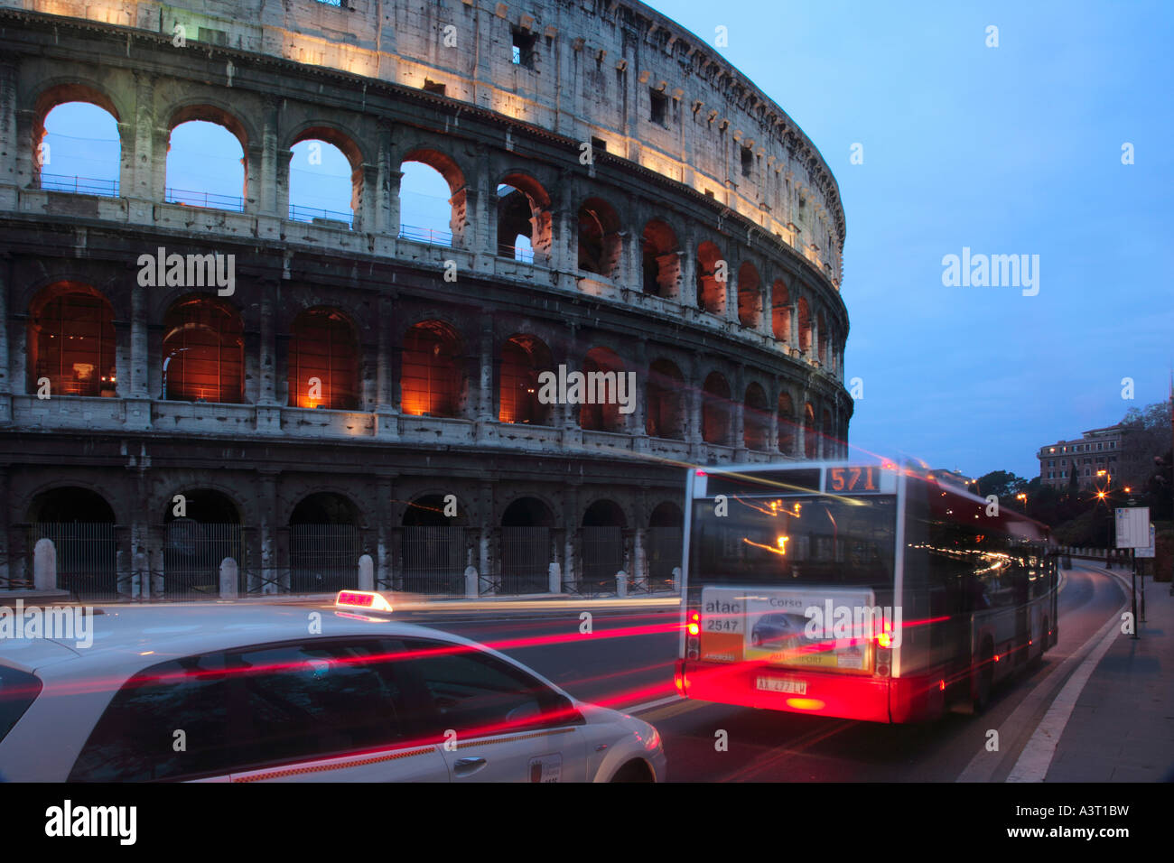 Bus and Taxi passing The Colosseum on the Via Dei Fori Imperiali in rush hour traffic Rome Italy - Stock Image