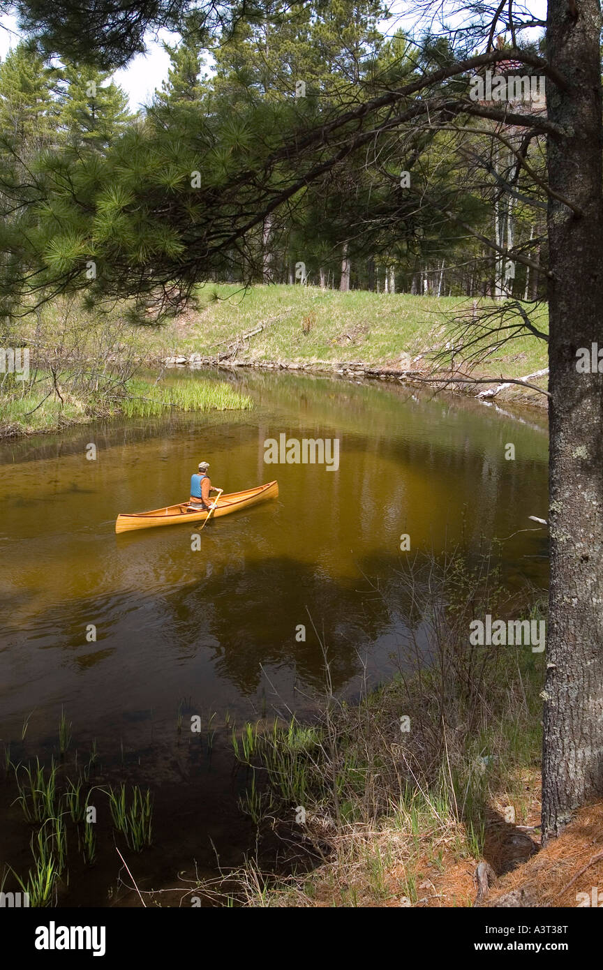 A solo canoeist paddles a cedar strip canoe on the AuTrain River in