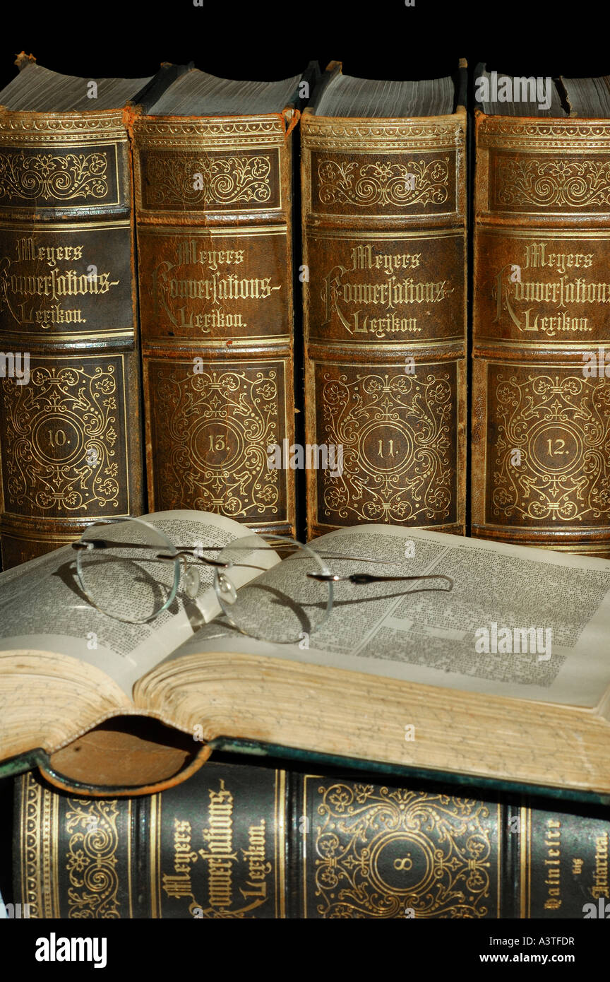 Reading glasses on open volume of an old edition of Meyers lexicon - Stock Image