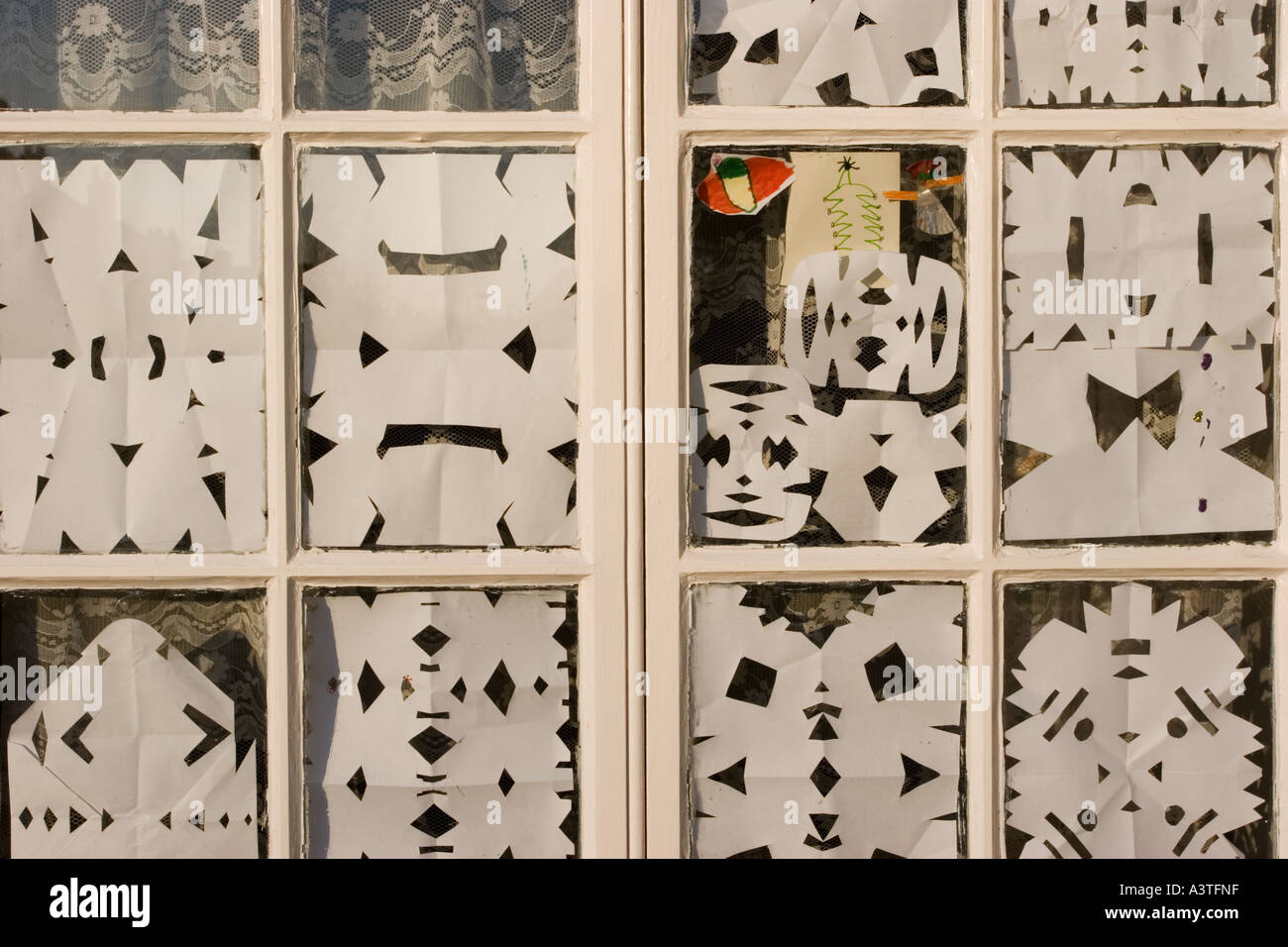 child s paper cutout snowflakes decorating a window at christmas