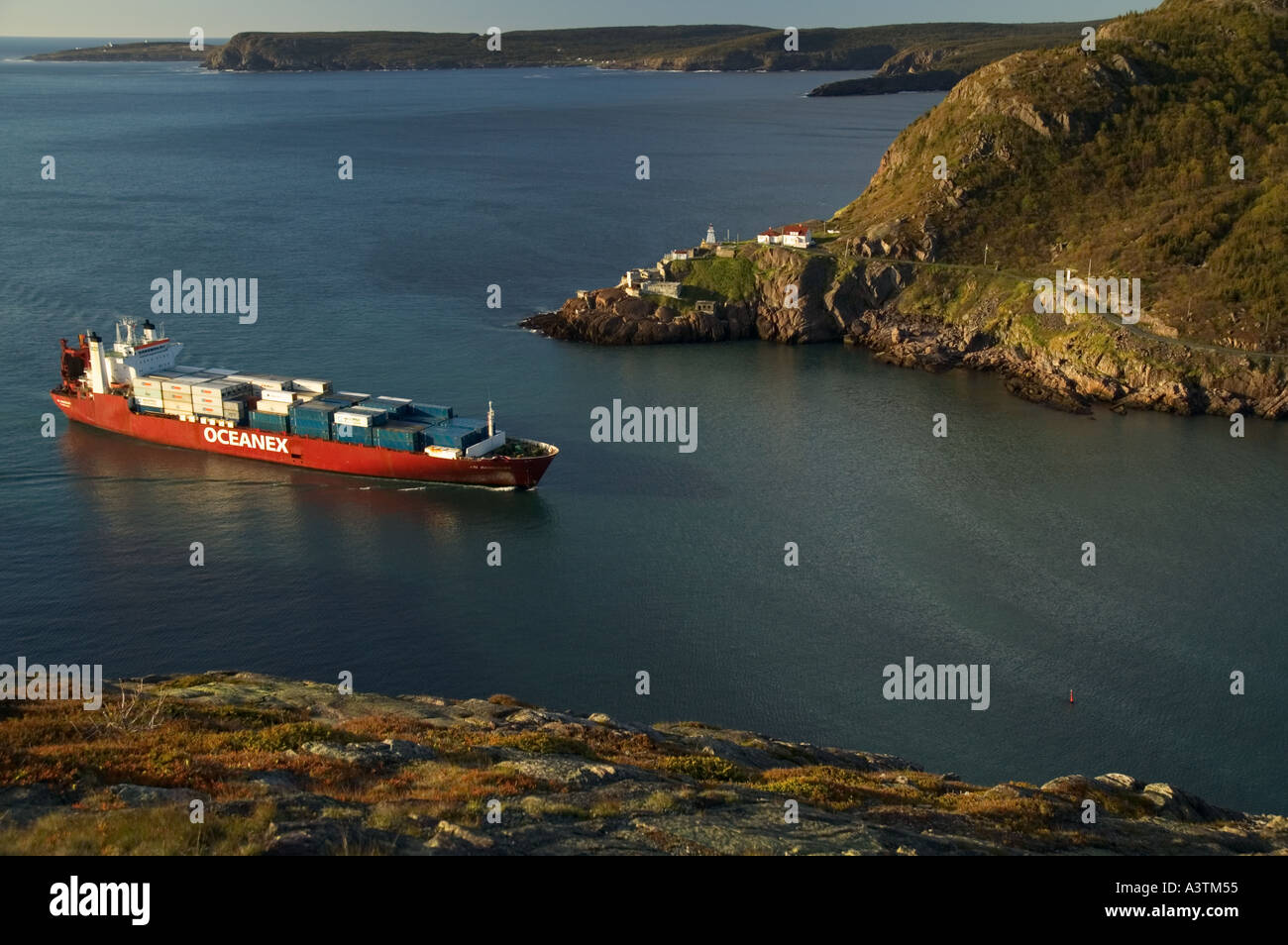 Canada Newfoundland St John s container ship entering harbour narrows Fort Amherst Lighthouse Stock Photo