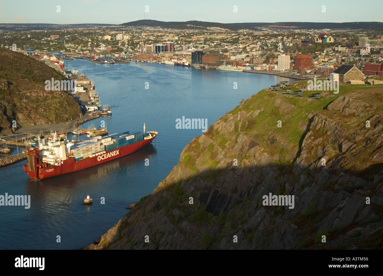 Canada Newfoundland St John s container ship entering harbour from narrows downtown skyline view from Signal Hill Stock Photo
