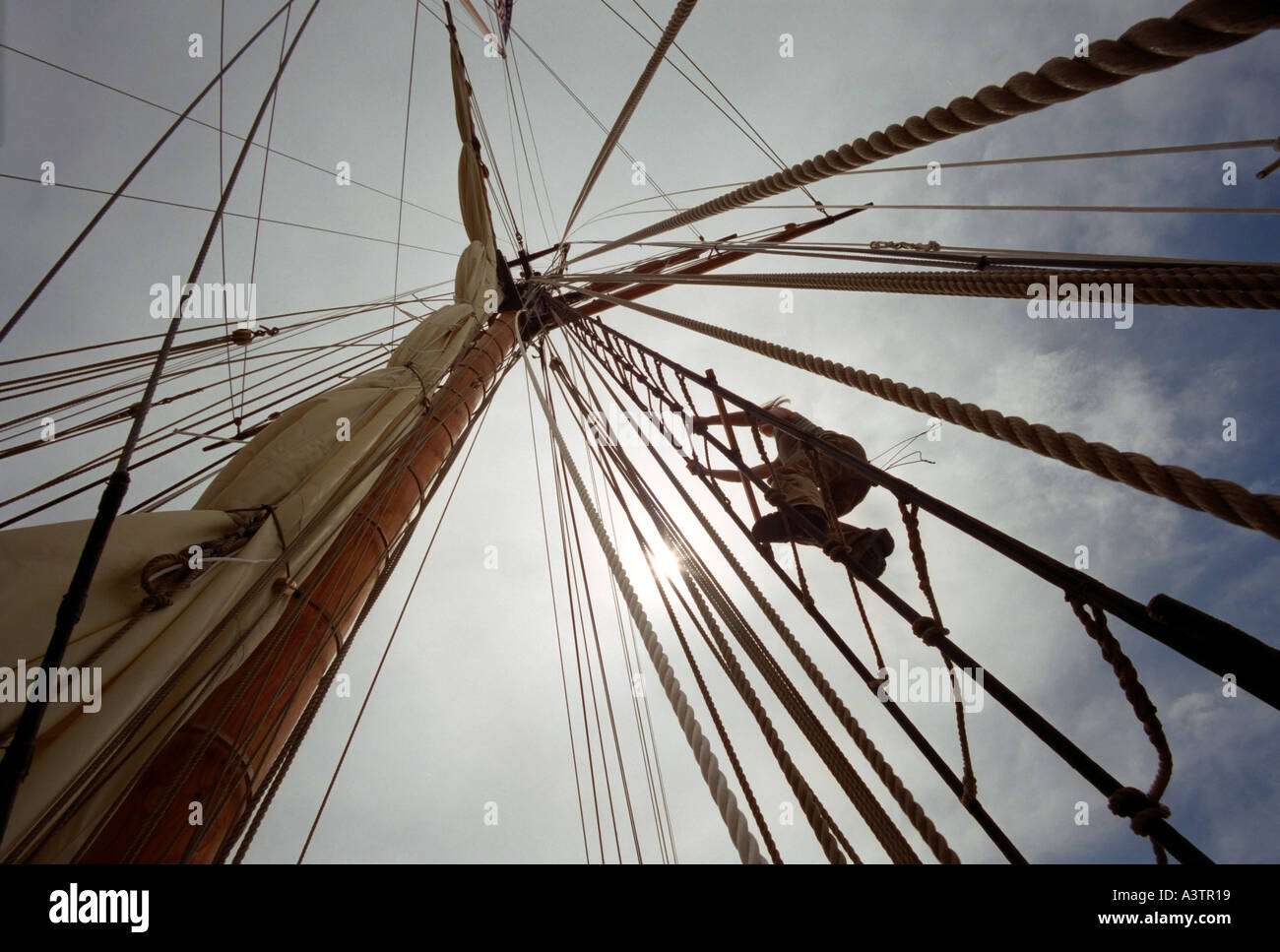 Photo of a Man climbing the mast of a tall sailing ship with sunlight - Stock Image