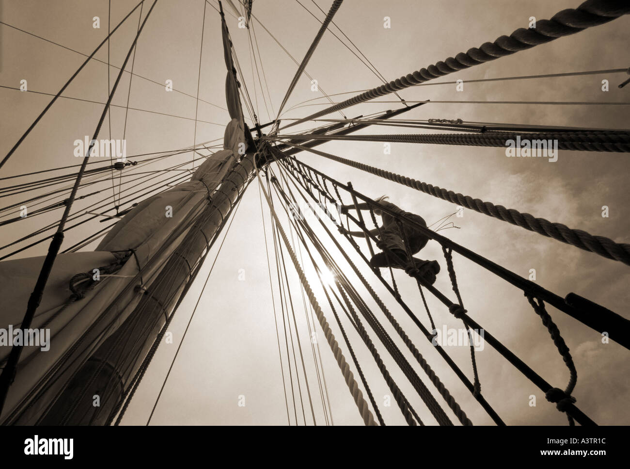 Photo of a Man climbing the mast of a tall sailing ship with sunlight sepia toned version - Stock Image