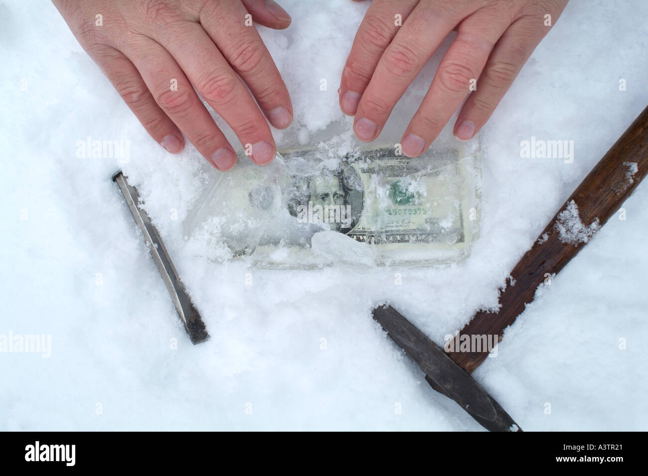 Hands finding money in frozen earth cold cash - Stock Image