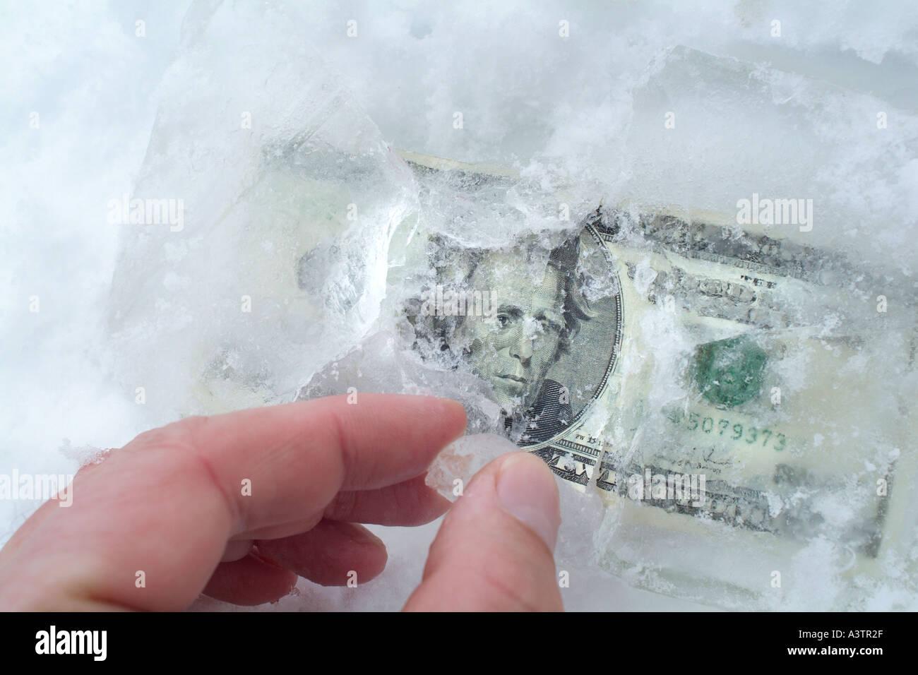 Hand finding frozen money in ice - Stock Image