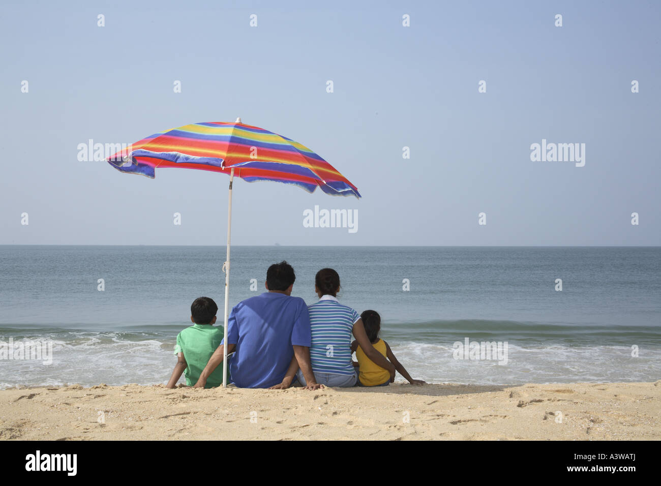 Family Of Four Sitting Below Umbrella On The Beach Lo Ng At The Sea
