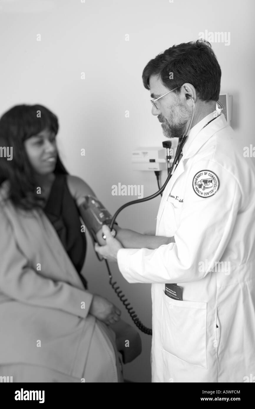 A Doctor examines a patient in a Connecticut Clinic in the USA. Many people in the USA have difficulty getting health - Stock Image