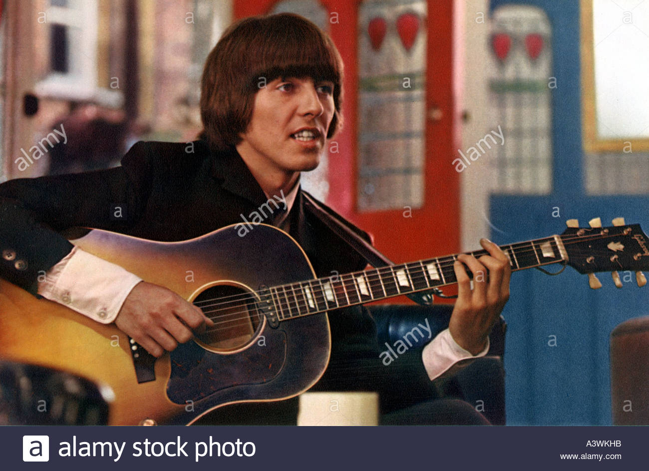 BEATLES - George Harrison with his Gibson acoustic guitar in the 1965 United Artists film HELP - Stock Image