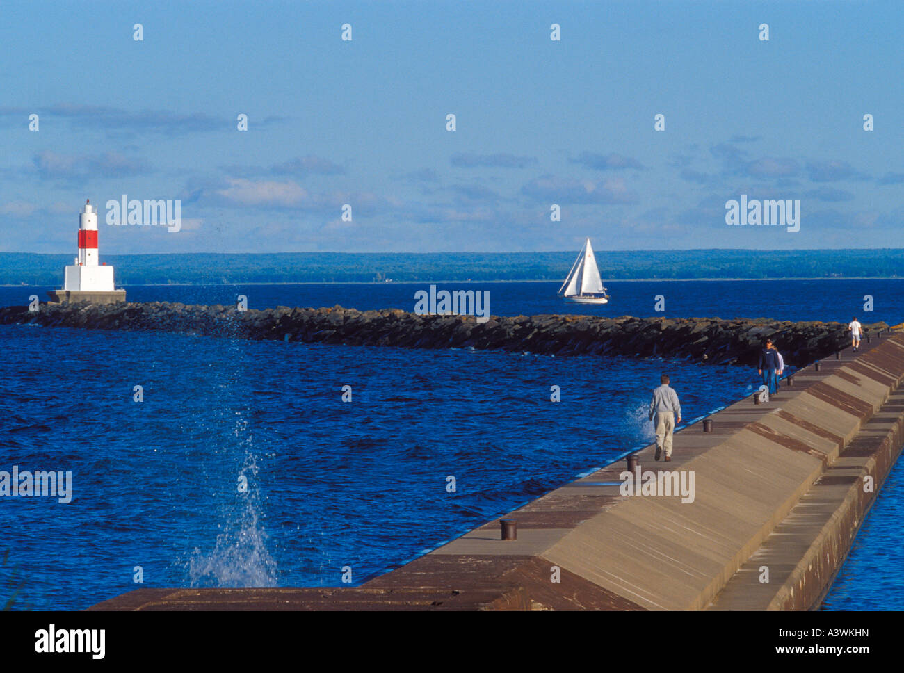Tourists walk the upper harbor breakwater in Marquette Mich as a sailboat leaves the harbor past the breakwater - Stock Image
