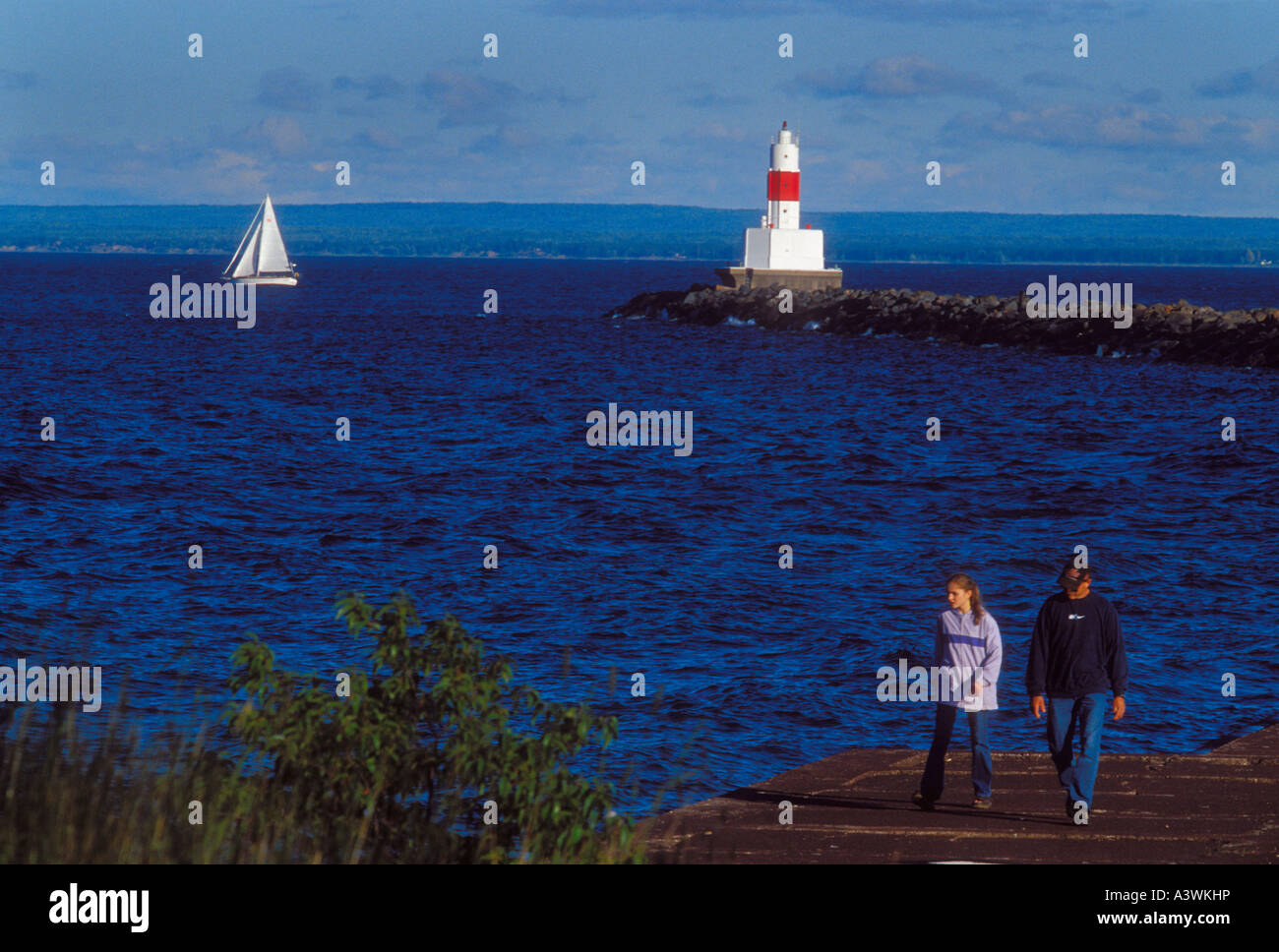 A sailboat passes the Upper Harbor breakwater light as tourists stroll the breakwater in Marquette Mich - Stock Image