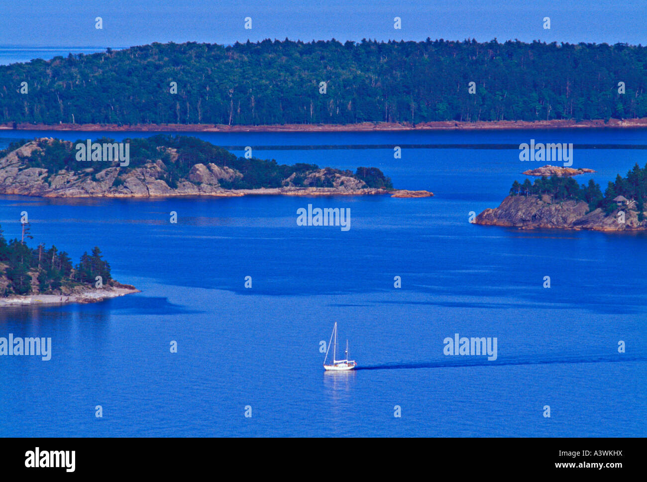 A sailboat cruises the waters of Lake Superior at Partridge Bay near Marquette Michigan - Stock Image