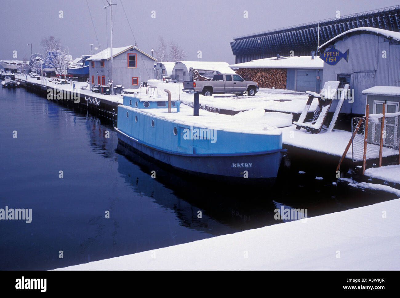 The fishing boat Kathy is covered with snow as she s docked at the Thill s Fish Dock in Marquette Mich - Stock Image