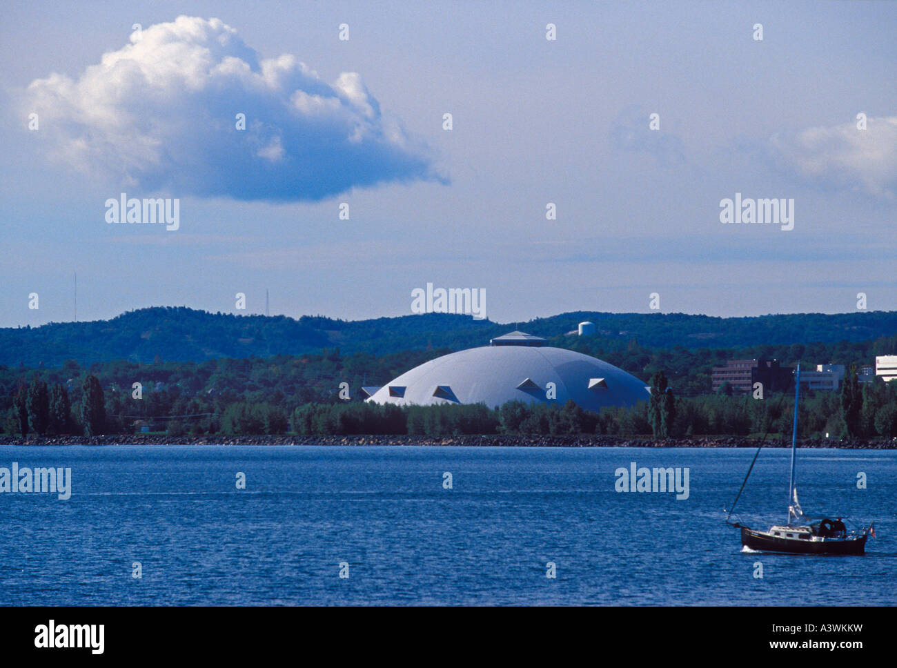 A sailboat motors out onto Lake Superior in Marquette Mich with a cloud and the NMU Superior Dome in the background - Stock Image