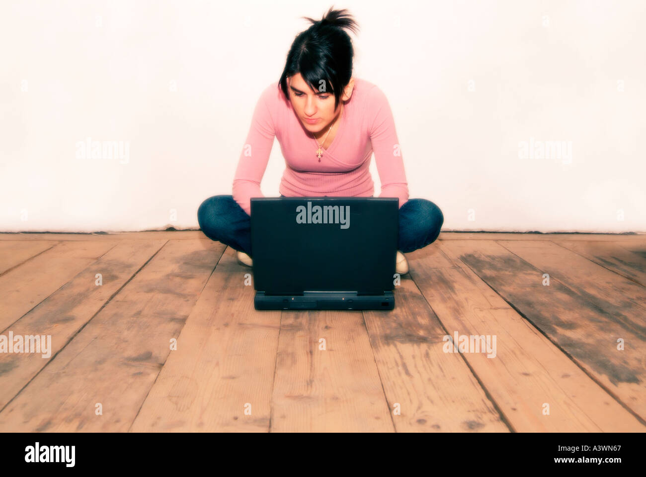 Woman Sat on Bare Wooden Floorboards Using a Laptop Stock Photo