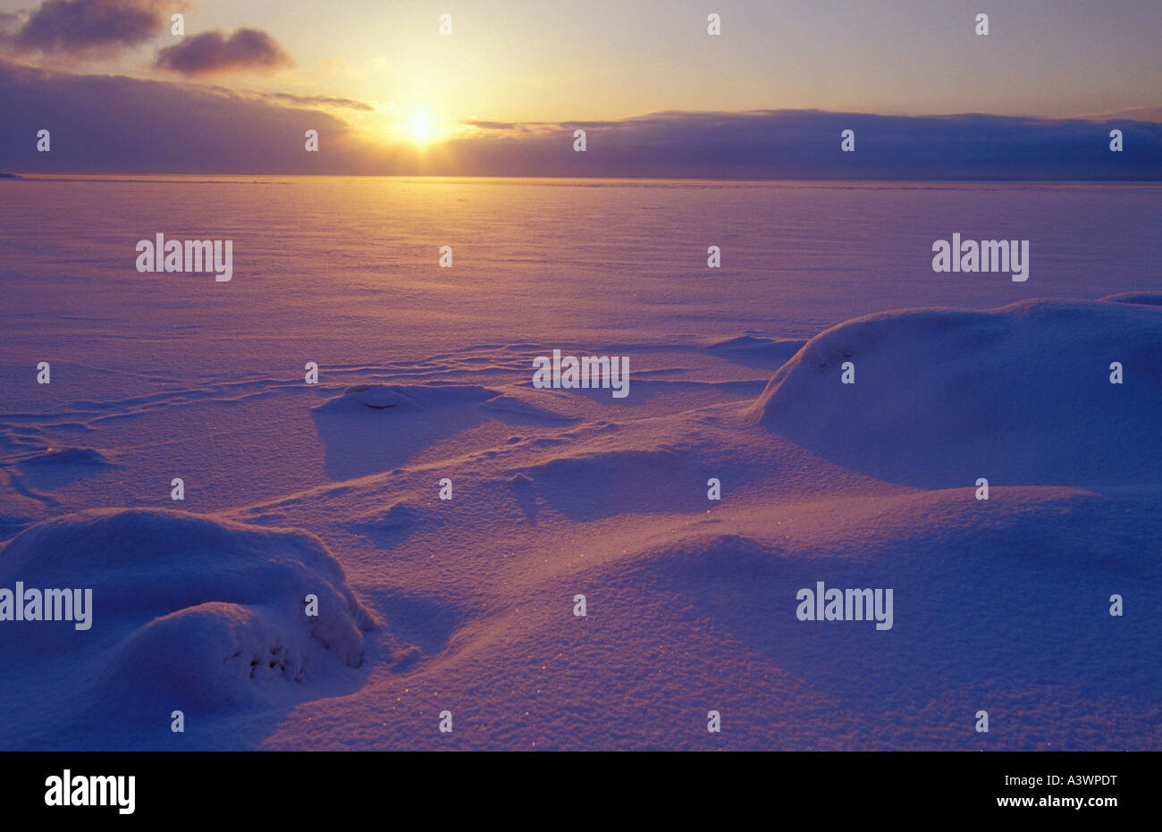 THE SUN RISES OVER FROZEN LAKE SUPERIOR COVERED WITH FRESH SNOW IN MARQUETTE MICHIGAN Stock Photo