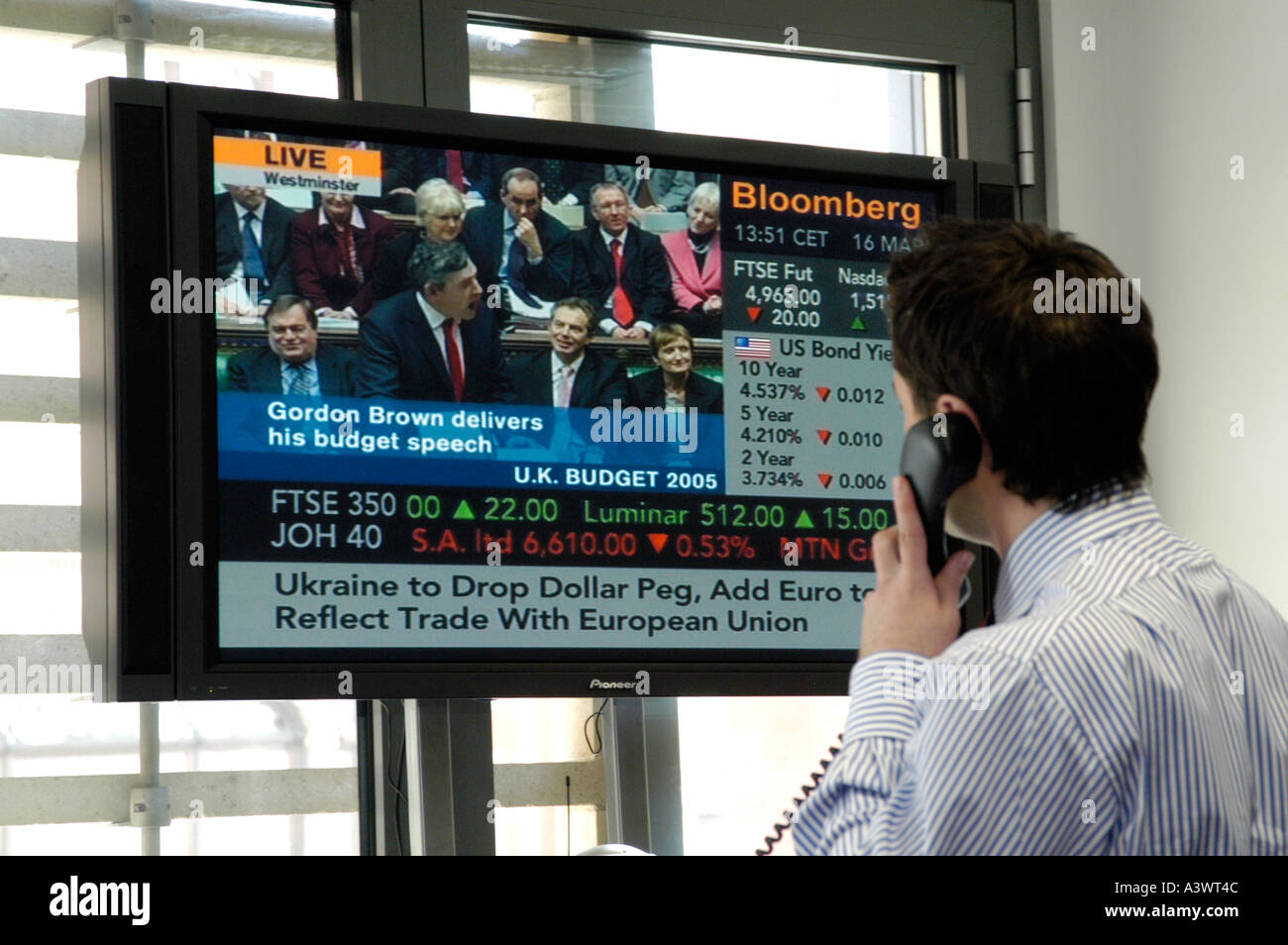 Currency trader watching Bloomberg business channel, London England Britain UK - Stock Image