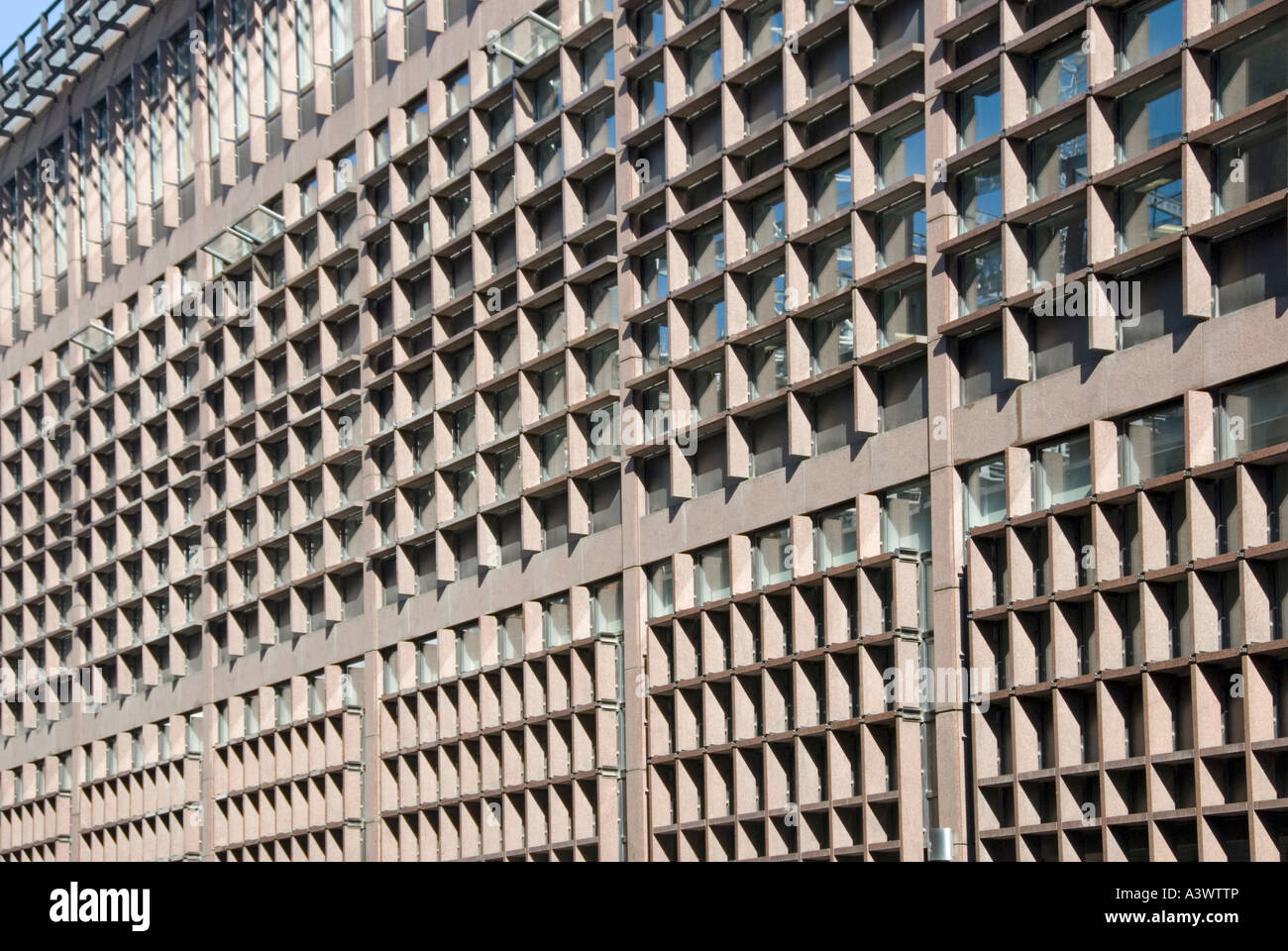 Repetitive visual pattern picture of office block elevation windows in deeply recessed squares and rectangles - Stock Image