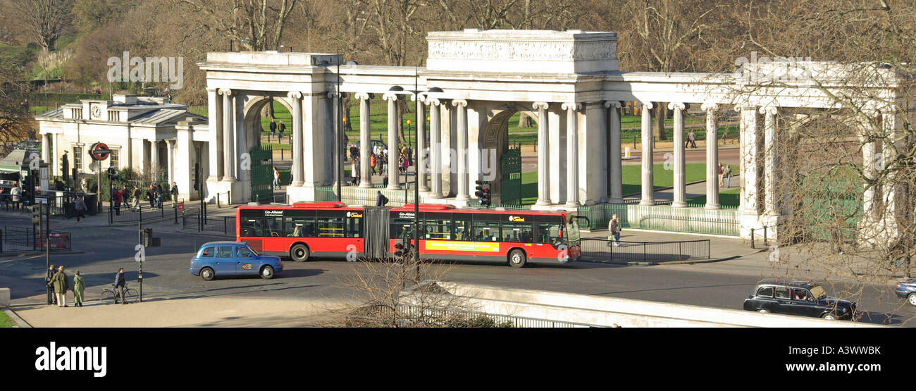 Bendy bus passing in front of the of the arch and columns of the Hyde Park Corner Screen London England UK - Stock Image