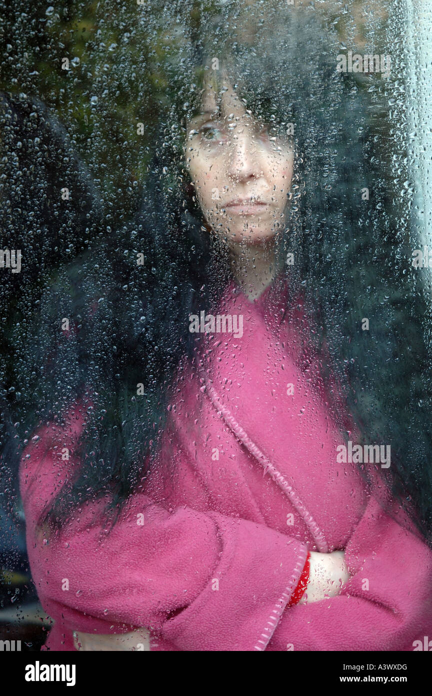 unhappy and depressed woman gazing through rain splashed window pane - Stock Image