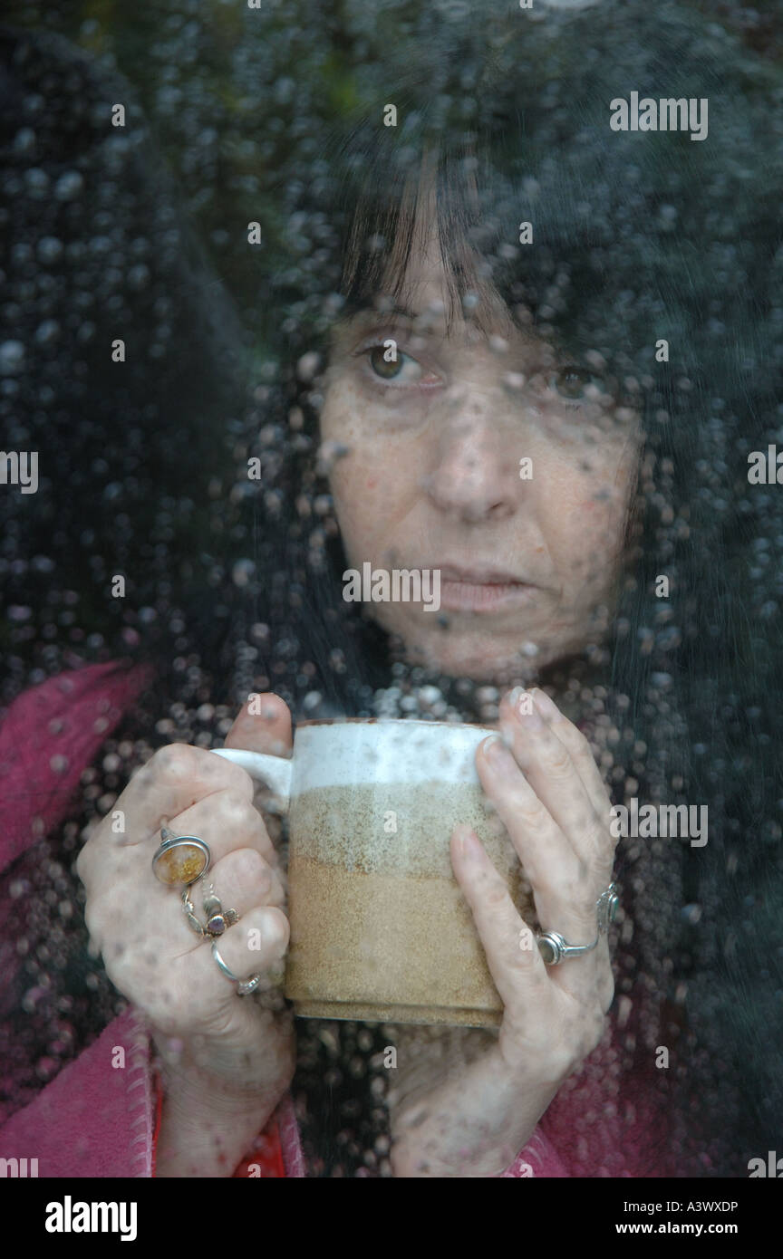 woman holding coffee mug staring through rain splashed window pane in winter - Stock Image