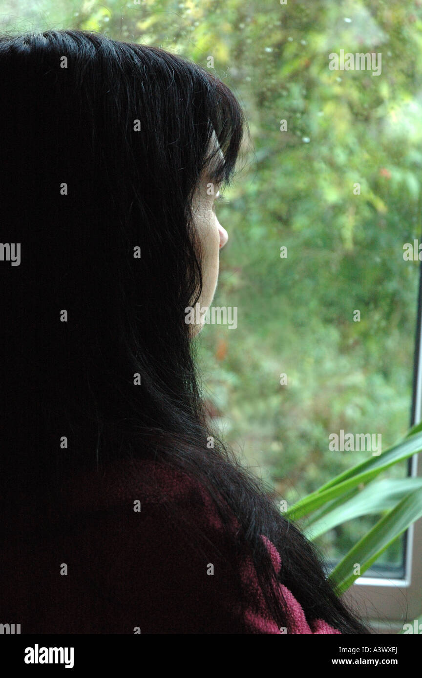 woman staring out of a rain splashed window in winter Stock Photo