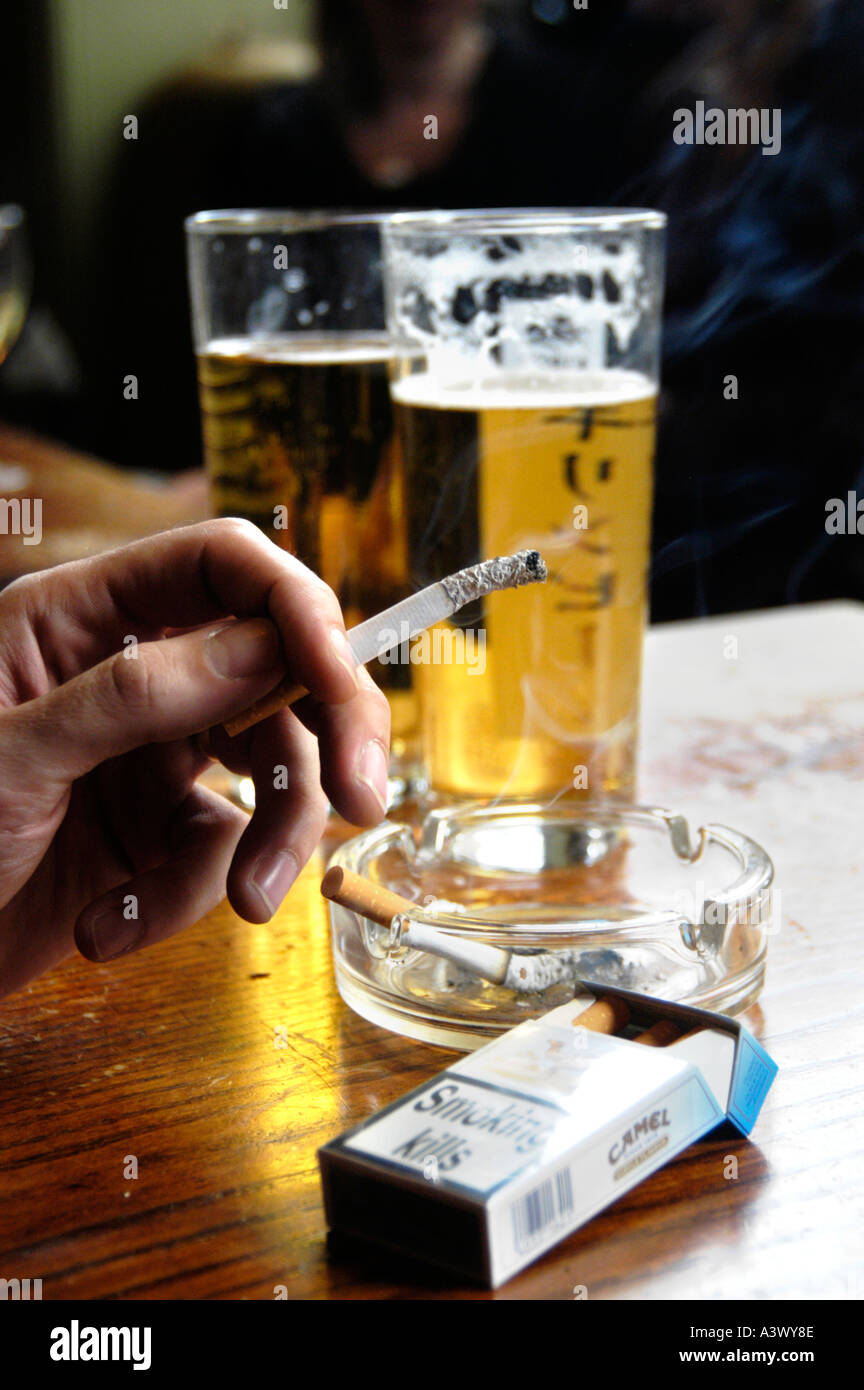 Smoking cigarette in a smoky pub with pint glasses of beer, UK - Stock Image