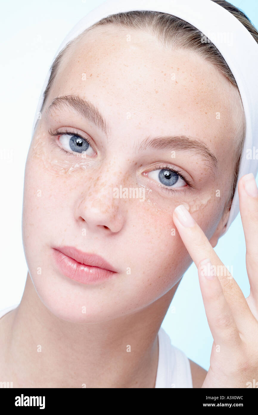 A young woman applying gel under her eyes close up - Stock Image