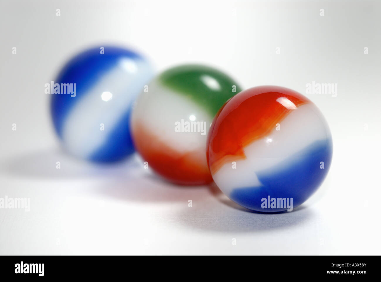 three marbles on a white surface Stock Photo