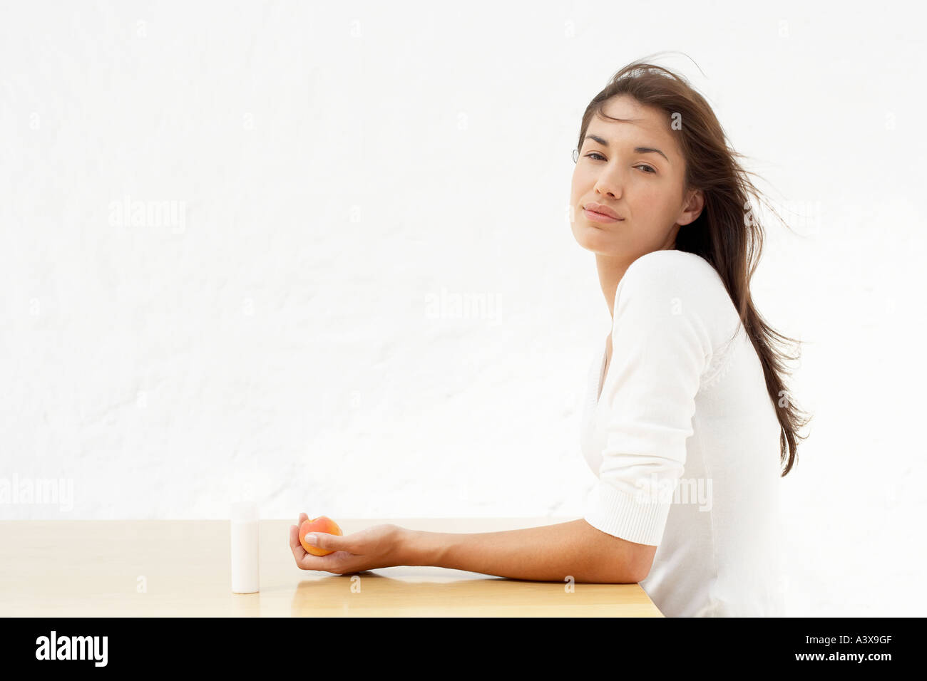A young woman holding an apricot rests beside a bottle of spray - Stock Image
