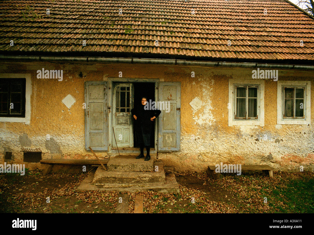 An old woman outside her cottage in Kosovo Stock Photo